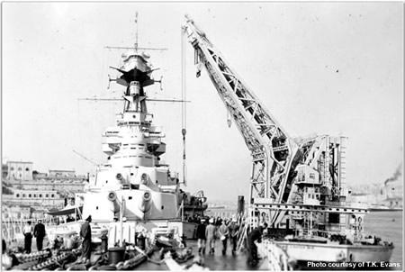"""Crane lifting a 4"""" gun aboard Hood"""