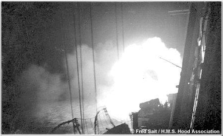 H.M.S. Hood firing her guns at night