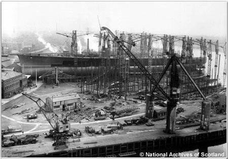 The immense hull of H.M.S. Hood dominates the Clydebank shipyard prior to launching