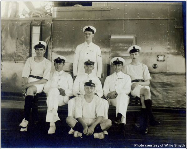 Crewmen aboard Hood, summer 1924. They are sitting on the starboard side of the Shelter Deck, abreast the after superstructure